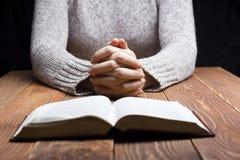 La femme remet la prière avec une bible dans l'obscurité plus de Photos stock
