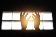 La femme remet la prière pour bénir d'un dieu dans la chambre sur le fond sombre Photo stock