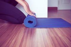 La femme remet le roulement ou le pliage tapis bleu de yoga sur le plancher de parquet après une séance d'entraînement photographie stock libre de droits