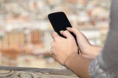 La femme remet le service de mini-messages à un téléphone intelligent Photographie stock libre de droits