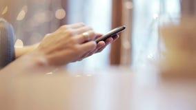 La femme remet le service de mini-messages, utilisant le smartphone en café banque de vidéos