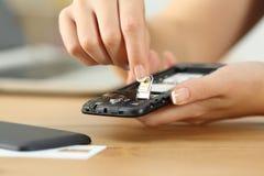 La femme remet mettre la carte de sim au téléphone photo libre de droits