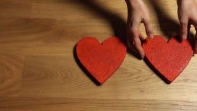 La femme remet mettre trois formes rouges de coeur sur la table en bois Famille, soin, concepts de cardiologie vidéo 4K banque de vidéos