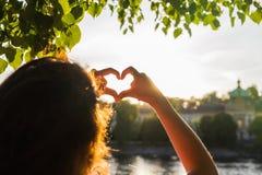 La femme remet montrer la forme d'un coeur sur le coucher du soleil, seul voyage de jeune femme, concept d'amour Image stock