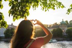 La femme remet montrer la forme d'un coeur sur le coucher du soleil, seul voyage de jeune femme, concept d'amour Image libre de droits