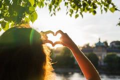 La femme remet montrer la forme d'un coeur sur le coucher du soleil, seul voyage de jeune femme, concept d'amour Photo stock