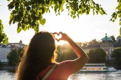 La femme remet montrer la forme d'un coeur sur le coucher du soleil, seul voyage de jeune femme, concept d'amour Photos stock