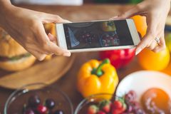 La femme remet prendre le fruit de photo avec le smartphone, concep de mode de vie Photos stock