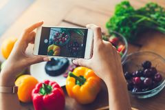 La femme remet prendre le fruit de photo avec le smartphone, concep de mode de vie Photo libre de droits