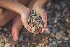La femme remet tenir de petites pierres dans des mains sur le fond de plage avec le soleil brûlant Photo stock