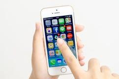 La femme remet tenir et toucher un iPhone 5s d'Apple Photo stock