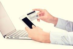 La femme remet tenir la carte de crédit utilisant la cellule, ordinateur intelligent de téléphone photos stock