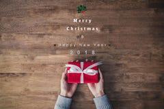 La femme remet tenir le boîte-cadeau rouge sur une table avec des textes de Joyeux Noël et de bonne année 2018 image stock