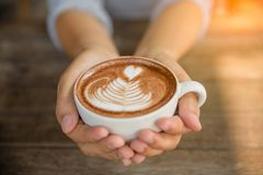 La femme remet tenir la tasse de cappuccino chaud de latte de café Photo libre de droits