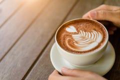 La femme remet tenir la tasse de cappuccino chaud de latte de café Images libres de droits