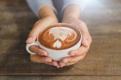 La femme remet tenir la tasse de cappuccino chaud de latte de café Photo stock