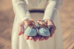 La femme remet tenir une paire de chaussures de bébé Photos stock