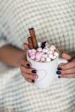 La femme remet tenir une tasse de chocolat chaud avec des guimauves Image libre de droits
