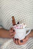 La femme remet tenir une tasse de chocolat chaud avec des guimauves Images stock