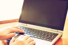 La femme remet travailler sur l'ordinateur portable près de la fenêtre avec la lumière naturelle Photo stock