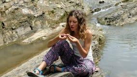 La femme repose sur des pierres et mange des figues le divisant dans la moitié et apprécie le fruit mûr en parc banque de vidéos