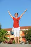 La femme reste et soulève heureusement des mains vers le haut Photos libres de droits