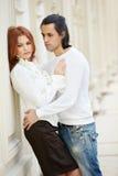 La femme reste, se penchant au mur et l'homme l'embrasse Photographie stock