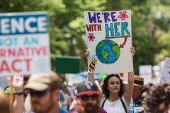 La femme retarde le signe marchant au jour de terre d'Atlanta mars Photographie stock libre de droits
