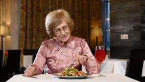 La femme retirée s'assied dans le restaurant avec de la salade végétale et un verre de boisson de fruit frais sur la table Modèle banque de vidéos