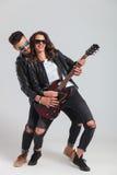 La femme riante joue la guitare électrique avec son homme Photographie stock libre de droits