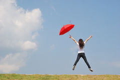 La femme rouge de parapluie sautent au ciel Photo libre de droits