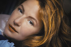 La femme rousse avec les lèvres rouges regarde par l'appareil-photo Image stock