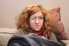 La femme rousse avec un oeil a fermé la détente sur le sofa Image libre de droits