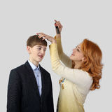 La femme rousse corrige la coiffure d'adolescent Photo stock