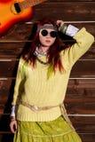 La femme rousse de boho hippie gai dans des lunettes de soleil pose sur un fond en bois de mur Images stock