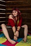 La femme rousse de boho hippie gai pose avec la vieille valise sur un fond en bois de mur Image stock