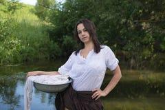 La femme rurale lave des vêtements en rivière Images libres de droits