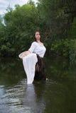 La femme rurale lave des vêtements en rivière Image libre de droits