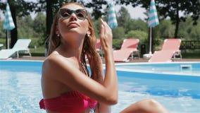 La femme sèche ses cheveux près de la piscine banque de vidéos