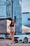 La femme séduisante de brune s'est habillée dans des vêtements modernes tient le sac à main posant près de la voiture de luxe con photos libres de droits