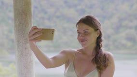 La femme séduisante posant pour la photo de selfie par le téléphone portable sur la colline verte a couvert la prise de touristes banque de vidéos