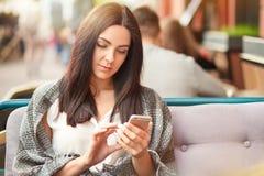 La femme sérieuse de brune lit le message de revenu au téléphone portable moderne, habillé en passant, téléphone portable moderne photographie stock libre de droits