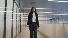 La femme sûre d'affaires utilise un téléphone portable fille dans un costume marchant par un immeuble de bureaux banque de vidéos