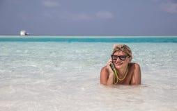 La femme s'étend dans les eaux bleues de l'Océan Indien et parle par téléphone Photographie stock