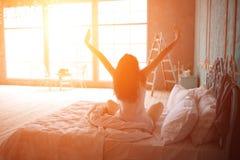 La femme s'étirant dans le lit après se réveillent Photo libre de droits