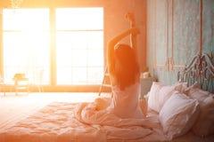La femme s'étirant dans le lit après se réveillent Photographie stock libre de droits