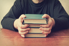 La femme s'asseyant à la table et garde une pile de vieux livres Photo stock