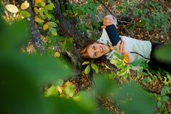 La femme s'asseyant dans un arbre parlant sur son phoneWoman futé s'est élevée dans un arbre prenant un autoportrait Image libre de droits