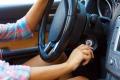 La femme s'asseyant dans un convertible et va mettre en marche le moteur Image stock