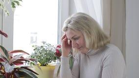 La femme s'asseyant par s'inquiéter de fenêtre frotte son front et est nerveuse clips vidéos